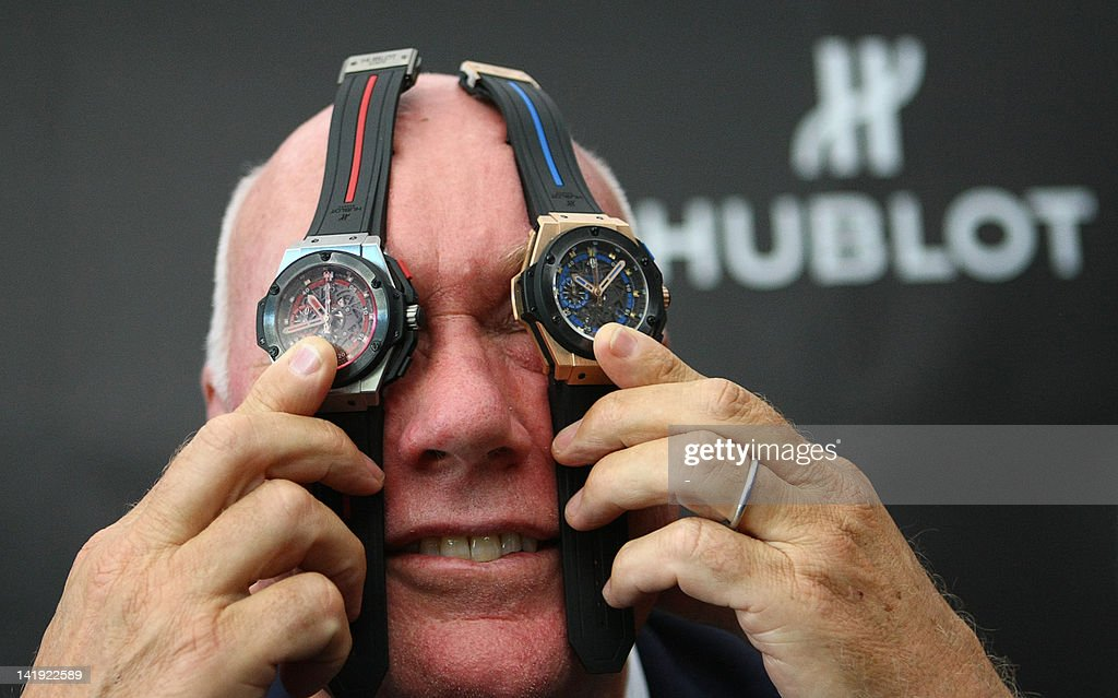 The chairman of Swiss watchmaker Hublot, Jean-Claude Biver, holds King Power UEFA Euro 2012 watches on March 26, 2012 during the unveiling of the official sponsor's goods in Kiev. One of the watches features the blue of the Ukrainian flag and the other the red of the Polish flag.