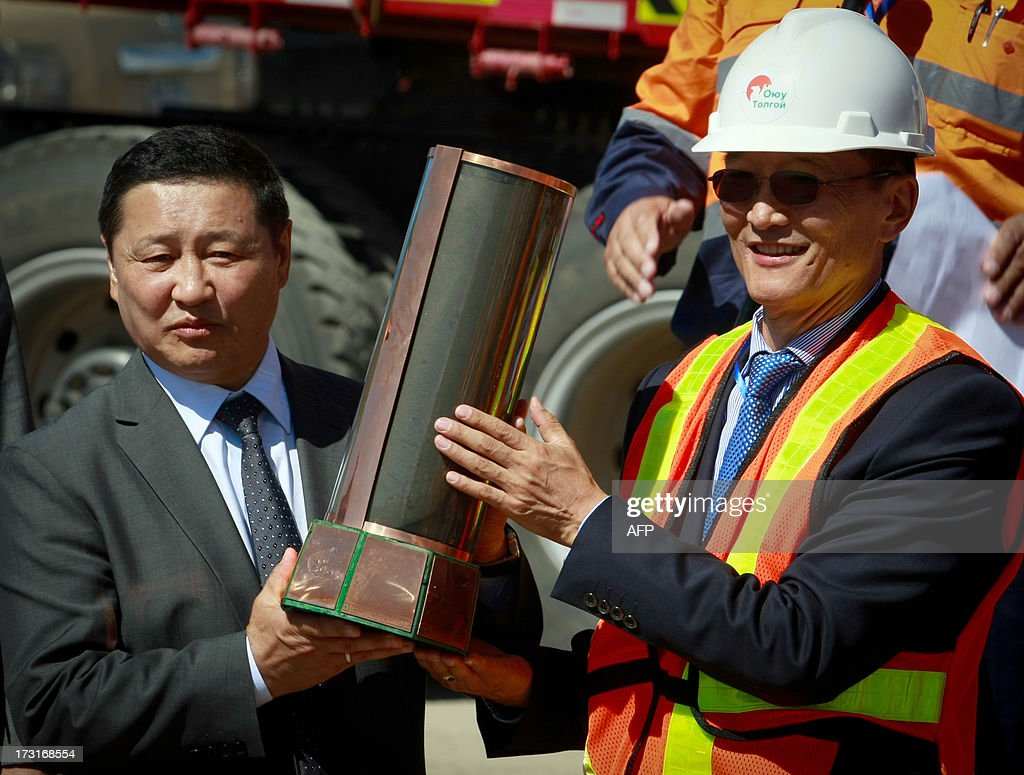 The Chairman of the Board of Directors of Oyu Tolgoi mine, Galsan Batsukh (R), hands in the first sample from the Oyu Tolgoi copper concentrate to the Mongolian Prime Minister Norov Altankhuyag on July 9, 2013 in the Gobi desert in southern Mongolia. A huge 6.2 billion USD copper mine in Mongolia that could transform the sprawling nation's fortunes has started exports, resources giant Rio Tinto said on July 9.