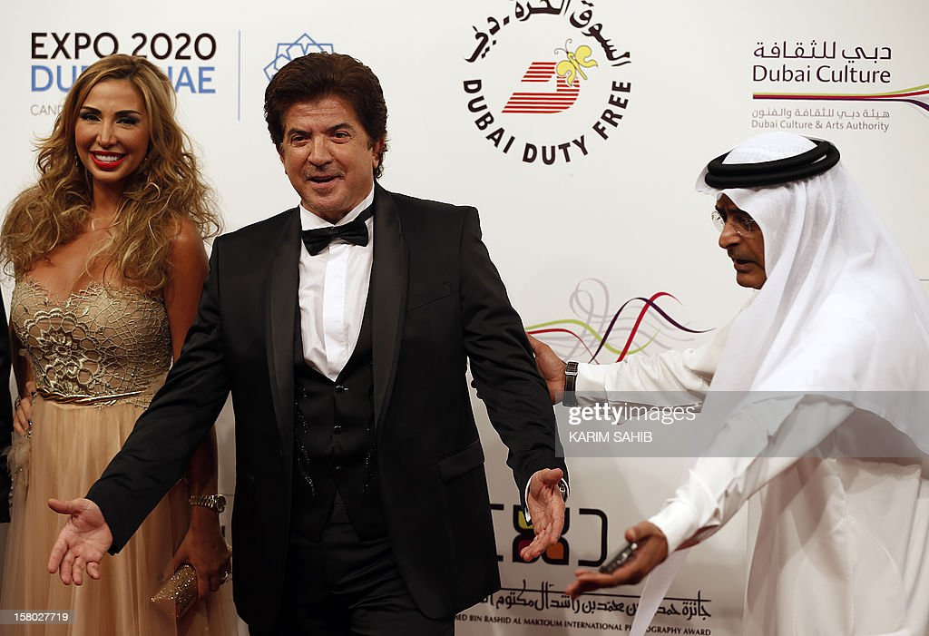 The Chairman of the Dubai International Film Festival Abdulhamid Juma (R) gestures as Lebanese singer Walid Toufic (L) poses for photographers and television presenter Joelle Mardinian (L) watches on during the opening ceremony of the Dubai International Film Festival in Gulf emirate of Dubai on December 9, 2012.