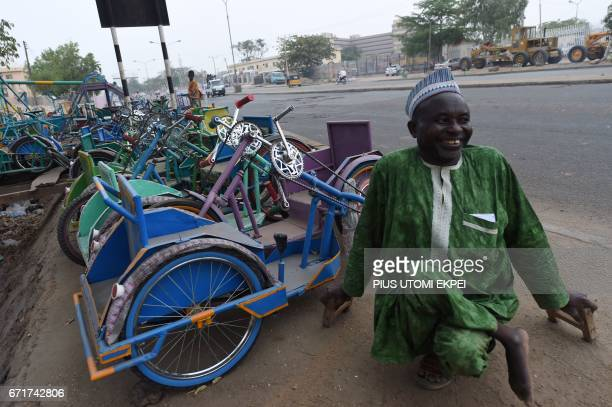 The Chairman of the Polio Victims Trust Association Aminu Ahmed poses with local tricycles fabricated by polio victim members on display for sale...