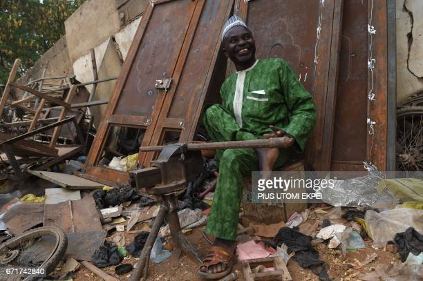 The Chairman of the Polio Victims Trust Association Aminu Ahmed sits in his workshop in Kano northwest Nigeria on April 21 2017 The World Health...