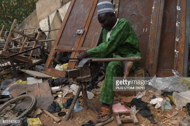 The Chairman of the Polio Victims Trust Association Aminu Ahmed tries to cut a metal for welding in their workshop in Kano northwest Nigeria on April...