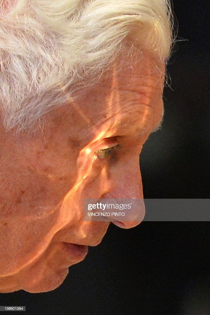 The chalice is reflected on Pope Benedict XVI's face during a Holy mass with new cardinals on November 25, 2012 at St Peter's basilica at the Vatican. Pope Benedict XVI the day before consecrated six non-European prelates as new members of the College of Cardinals in a development welcomed by critics concerned that the body which will elect the future pope is too Euro-centric. AFP PHOTO / VINCENZO PINTO