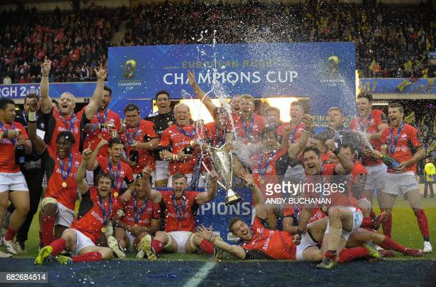 The champagne is sprayed as Saracens players celebrate their win with the trophy on the pitch after the rugby union European Champions Cup Final...
