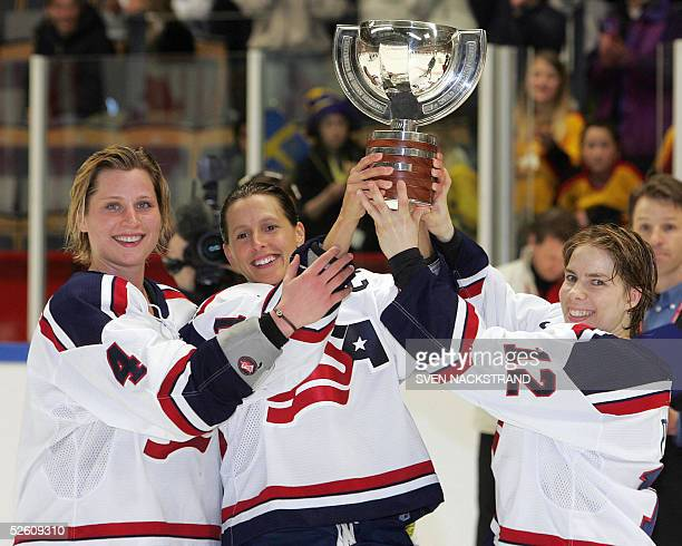 The Championship trophy is lifted by US captain Cammi Granato and assistant captains Jenny Potter and Angela Ruggiero after the USA beat Canada in...