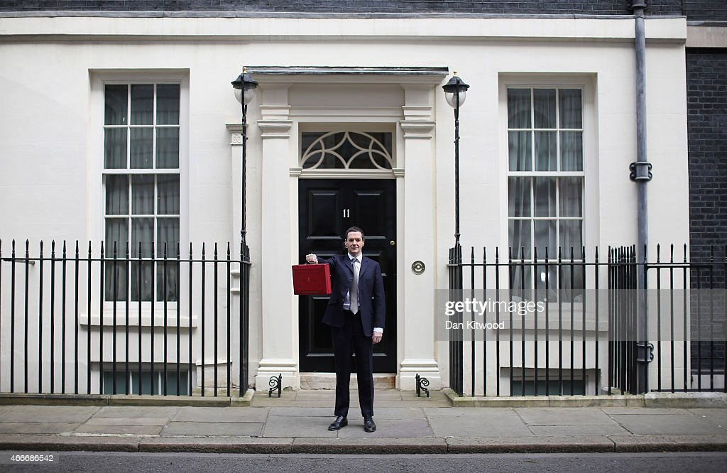 The Chancellor of the Exchequer George Osborne holds his ministerial red box up to the media as he leaves 11 Downing Street on March 18, 2015 in London, England. The Chancellor is presenting his 5th Budget to Members of Parliament today, the last before the General Election on May 7, 2015.