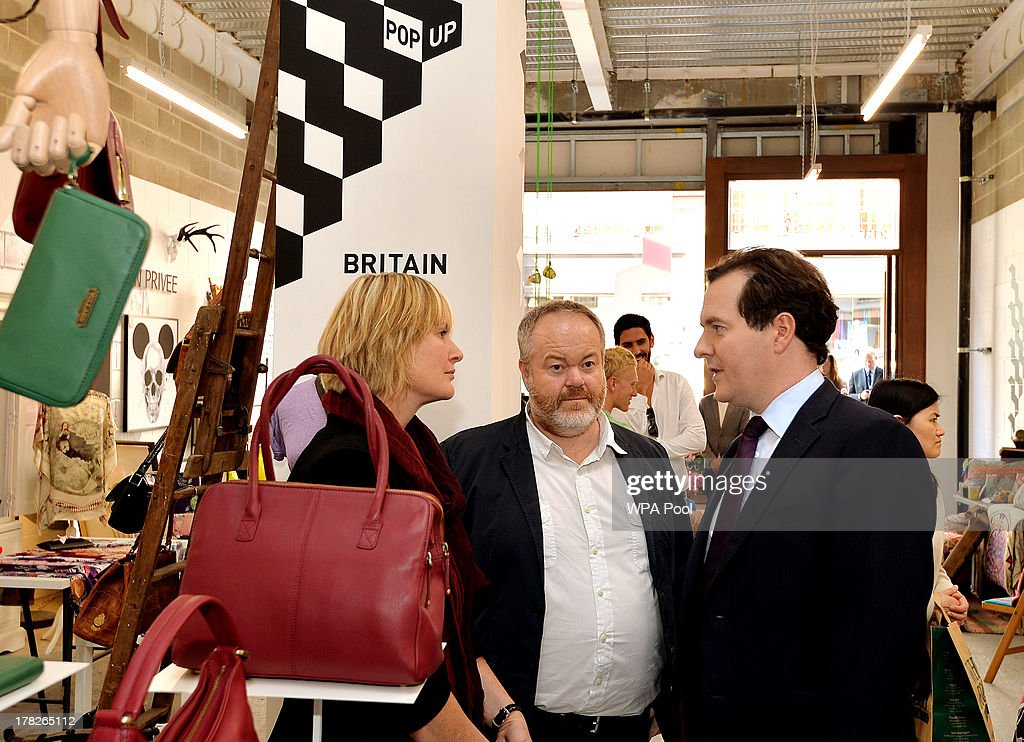 The Chancellor of the Exchequer George Osborne talks to Julia Dobson and Eddie Knevett (C) the owners of village England hand made handbags, during a visit to a pop up shop where ten new small companies are trying to produce growth and become established, on August 28, 2013 in Piccadilly, London.