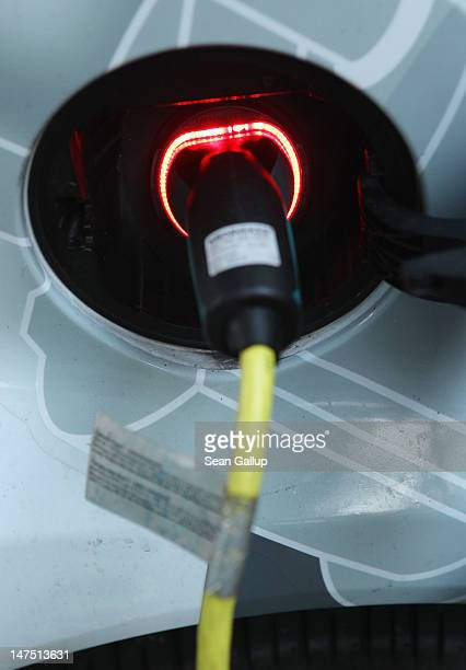 The charging port of an electric Smart car part of the Flinkster carsharing program of German state railway company Deutsche Bahn glows red while...