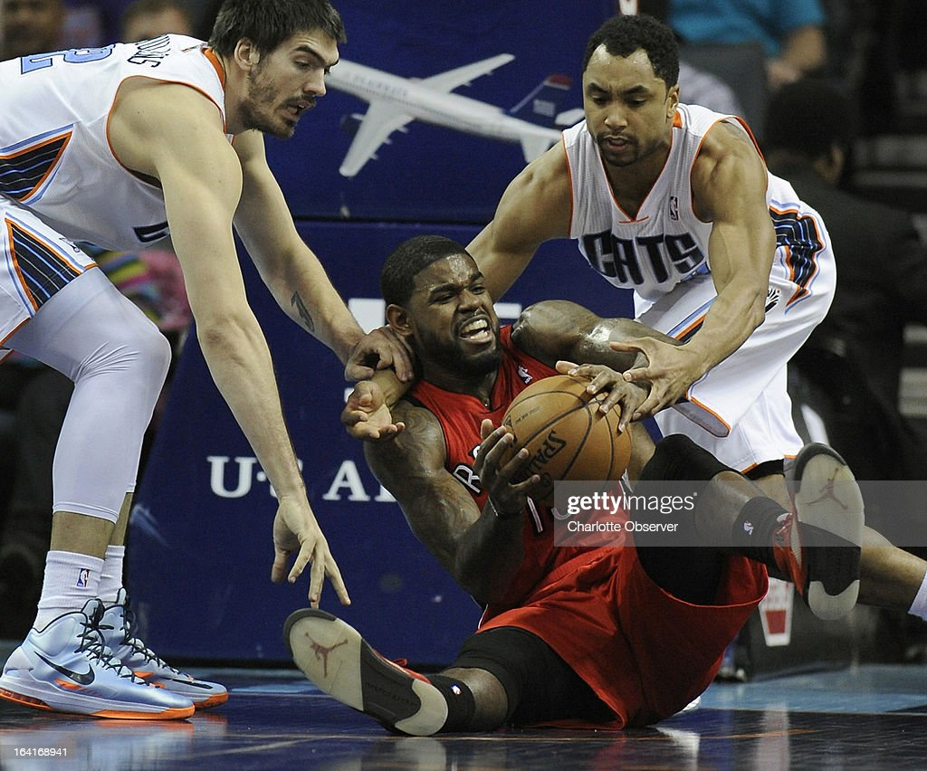 The Charlotte Bobcats' Byron Mullens, left, and Gerald Henderson, right, try to strip the ball from the Toronto Raptors' Amir Johnson during first-half action at Time Warner Cable Arena in Charlotte, North Carolina, on Wednesday, March 20, 2013.