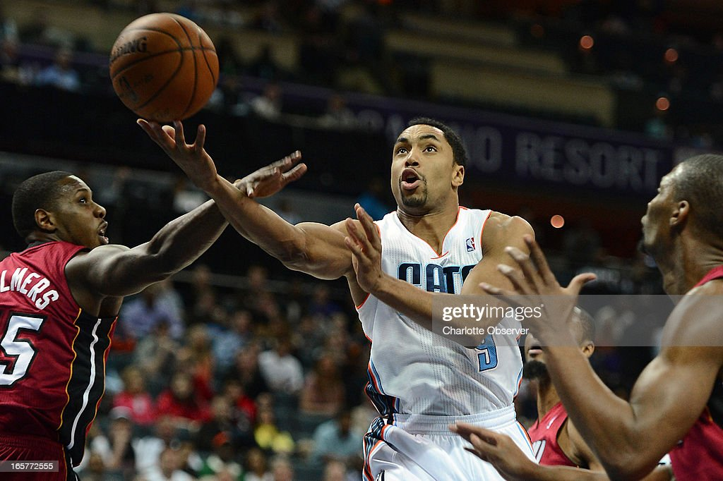 The Charlotte Bobcats' Gerald Henderson drives to the basket between Miami Heat defenders Mario Chalmers, left, and Chris Bosh during first-half action on Friday, April 5, 2013 at Time Warner Cable Arena in Charlotte, North Carolina.