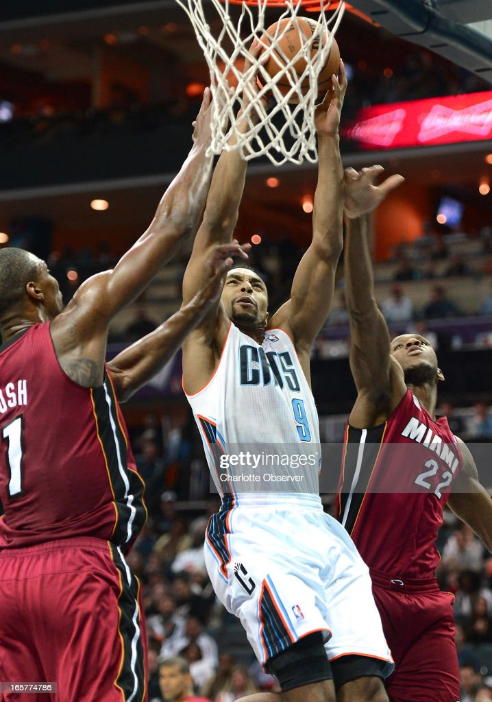 The Charlotte Bobcats' Gerald Henderson fights his way to the basket as Miami Heat defenders Chris Bosh, left, and James Jones (22) during second-half action on Friday, April 5, 2013 at Time Warner Cable Arena in Charlotte, North Carolina. Miami won, 89-79.