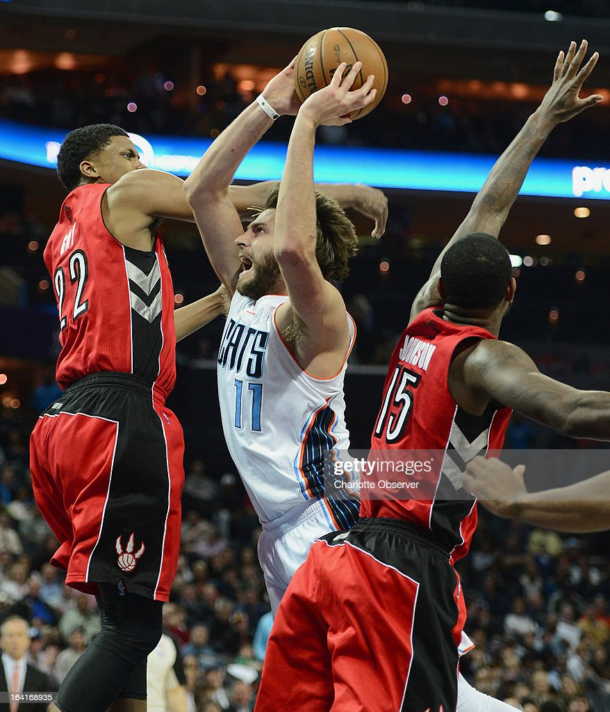 The Charlotte Bobcats' Josh McRoberts, middle, fights his way to the basket between the Toronto Raptors Rudy Gay, left, and Amir Johnson during first-half action at Time Warner Cable Arena in Charlotte, North Carolina, on Wednesday, March 20, 2013.