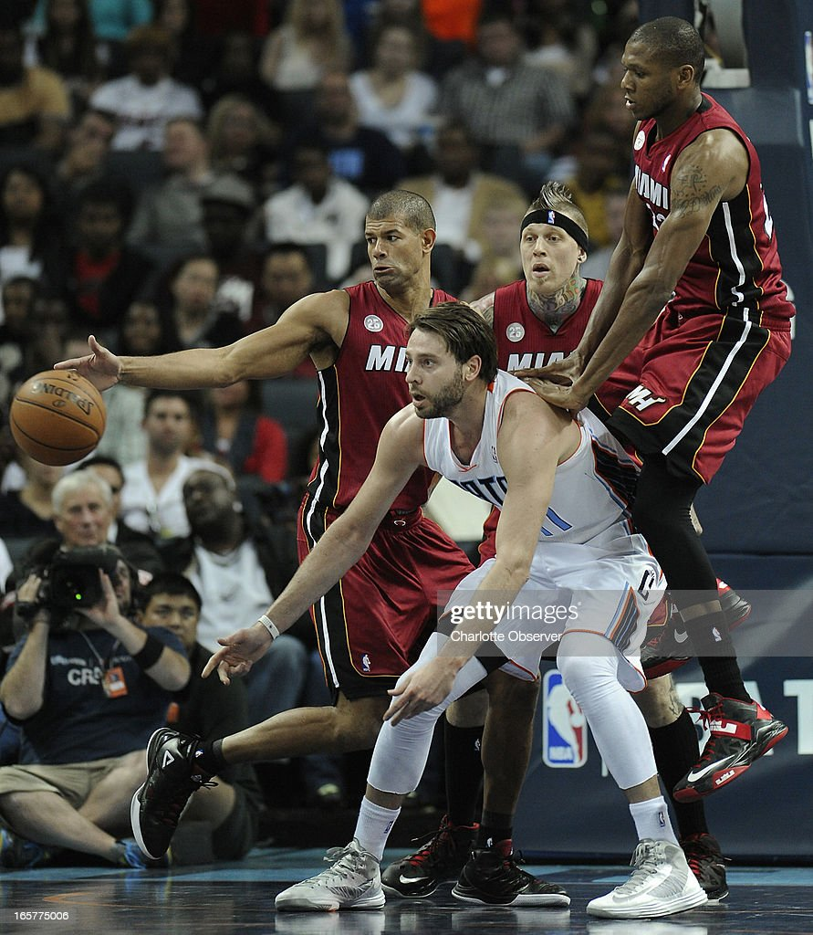 The Charlotte Bobcats' Josh McRoberts passes the ball to a teammate as the Miami Heat's, from left, Shane Battier, Chris Andersen and James Jones, defend during second-half action on Friday, April 5, 2013 at Time Warner Cable Arena in Charlotte, North Carolina. Miami won, 89-79.