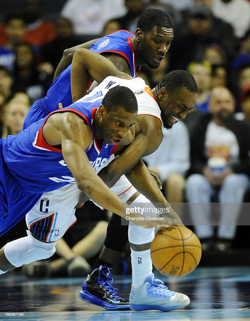 The Charlotte Bobcats' Kemba Walker goes between the Philadelphia 76ers' Thaddeus Young (21) and Royal Ivey, top, for a loose ball during the second half at Time Warner Cable Arena in Charlotte, North Carolina, on Wednesday, April 3, 2013. Charlotte prevailed, 88-83.