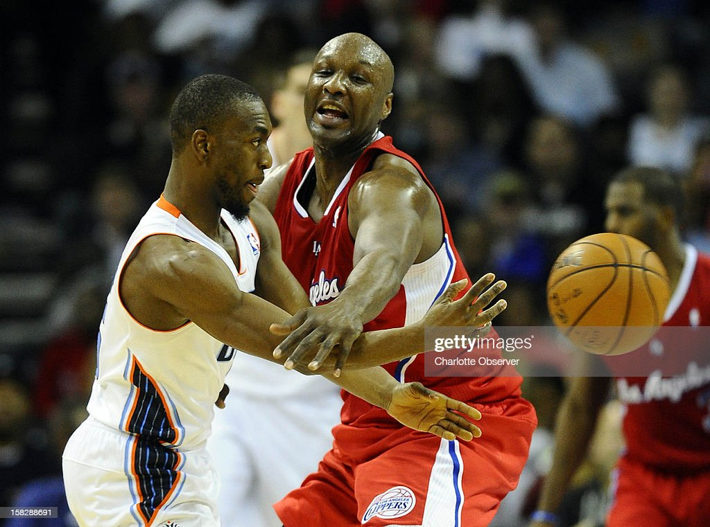 The Charlotte Bobcats' Kemba Walker, left, passes around Lamar Odom of the Los Angeles Clippers in the second half at Time Warner Cable Arena in Charlotte, North Carolina, on Wednesday, December 12, 2012. The Clippers won, 100-94.
