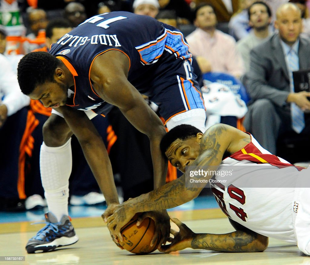 The Charlotte Bobcats' Michael Kidd-Gilchrist (14) and the Miami Heat's Udonis Haslem (40) scramble for control of the ball during the first half at Time Warner Cable Arena in Charlotte, North Carolina, on Wednesday, December 26, 2012.