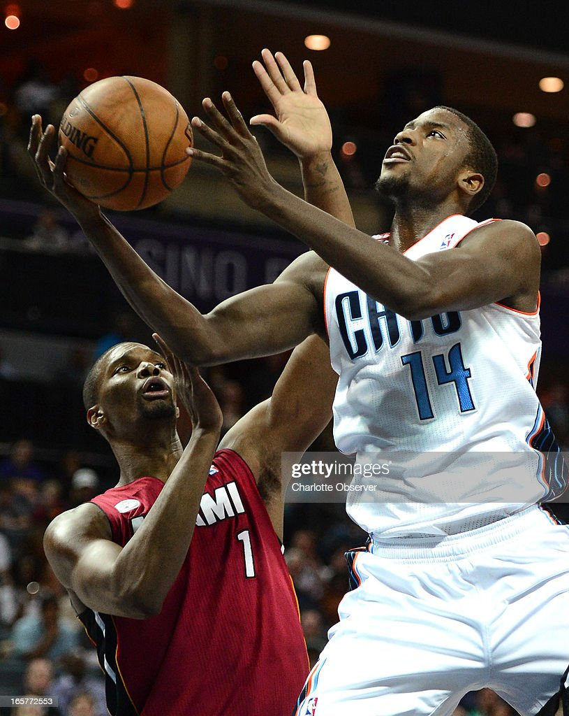 The Charlotte Bobcats' Michael Kidd-Gilchrist (14) fights his way to the basket as the Miami Heat's Chris Bosh applies defensive pressure during first-half action on Friday, April 5, 2013 at Time Warner Cable Arena in Charlotte, North Carolina.