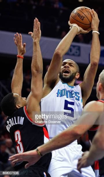 The Charlotte Hornets'Nicolas Batum releases a jumper against the Portland Trail Blazers' CJ McCollum left in the first half at the Spectrum Center...