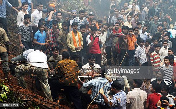 The charred body of a victim is carried from the site of the airline crash on May 22 2010 in Mangalore An Air India Express Boeing 737800 series...