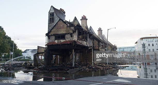The charred remains of the Reeves furniture store are pictured in Croydon south of London on August 9 following a third night of violence on the...