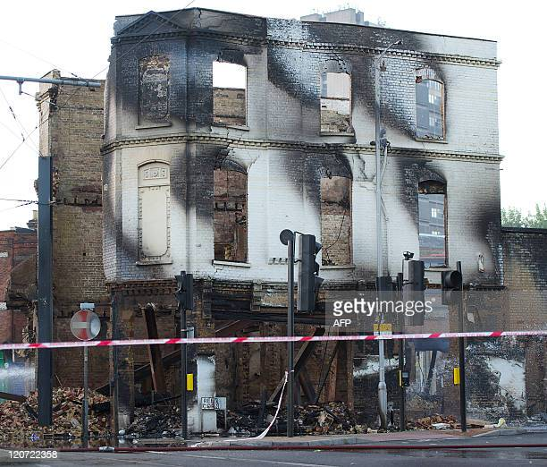 The charred remains of the Reeves furniture store is pictured in Croydon south of London on August 9 following a third night of violence on the...