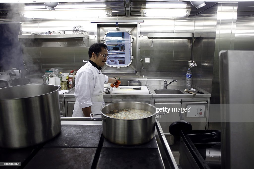 The chef works in the kitchens of the Marco Polo, flying a British flag and said to be the world's biggest container ship by French owners CMA CGM, moored in the port of Le Havre, western France, early on December 19, 2012. The Marco Polo was given its champagne christening in the Belgian port of Zeebrugge on December 18, 2012. The ship, which is 396 metres (yards) long -- the length of four football fields -- was built in South Korea and was to head back to Asia after a stop in France. It is said to be the largest container in the world measured by capacity, as it can hold 16,020 TEU (twenty-foot equivalent unit containers) -- or 97 kilometres of containers lined up one by one.