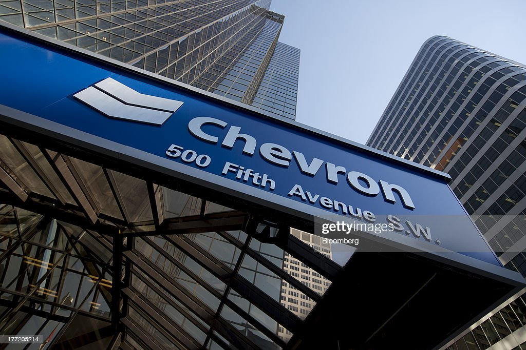The Chevron Corp logo sits on Chevron Plaza in Calgary Alberta Canada on Wednesday Aug 14 2013 Statistics Canada is scheduled to release June gross...