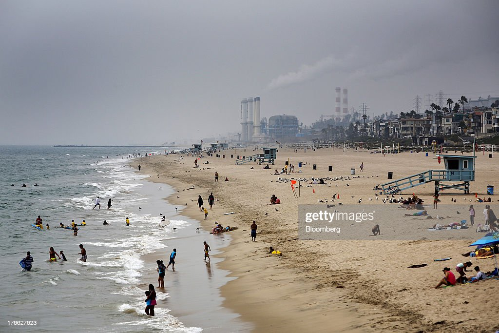 The Chevron El Segundo refinery stands in the background as beach goers bathe in the ocean in Manhattan Beach, California, U.S., on Wednesday, Aug. 14, 2013. Overall U.S. tourism-related sales increased 6.8% in the second quarter of 2013 as compared to 2012. Photographer: Patrick T. Fallon/Bloomberg via Getty Images