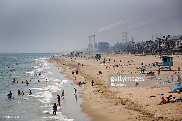 The Chevron El Segundo refinery stands in the background as beach goers bathe in the ocean in Manhattan Beach California US on Wednesday Aug 14 2013...
