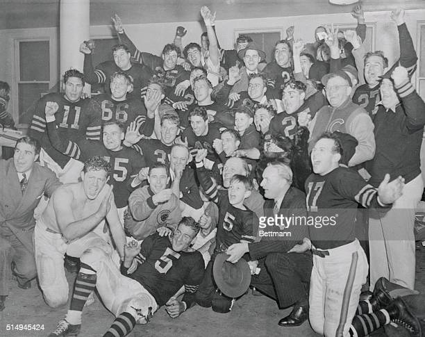 The Chicago Bears Champions of the National Professional Football League exult for photographers in their dressing room at Wrigley Field after...