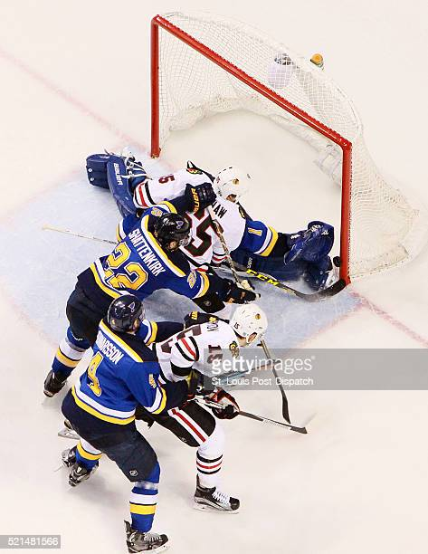 The Chicago Blackhawks' Andrew Shaw scores past St Louis Blues goaltender Brian Elliott as he takes a shove from Blues defenseman Kevin Shattenkirk...