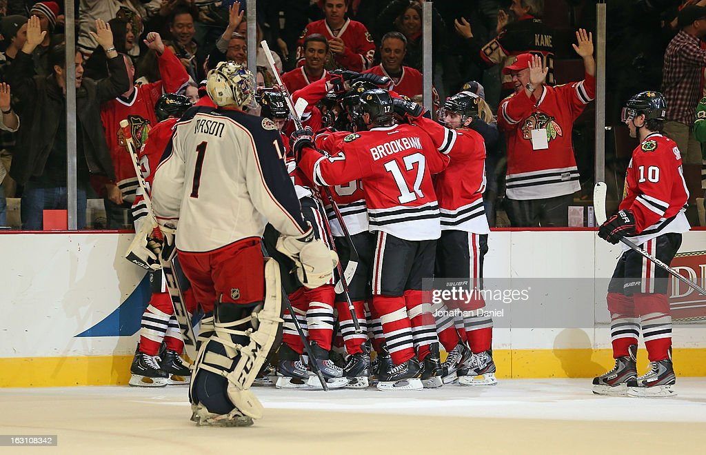 The Chicago Blackhawks celebrate a win as Steve Mason #1 of Columbus Blue Jackets skates back to the bench at the United Center on March 1, 2013 in Chicago, Illinois. The Blackhawks defeated the Blue Jackets 4-3 in overtime.