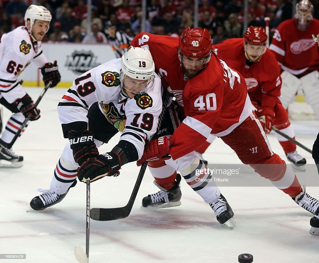The Chicago Blackhawks' Jonathan Toews (19) and Detroit Red Wings' Henrik Zetterberg (40) fight for the puck in the first period in Game 4 of the Western Conference semifinal at Joe Louis Arena in Detroit, Michigan, on Thursday, May 23, 2013.