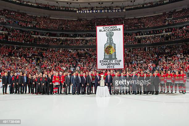 The Chicago Blackhawks pose for a photo with the Stanley Cup Championship banner during pregame ceremonies of the season opener against the New York...