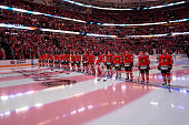The Chicago Blackhawks stand for the national anthem prior to the NHL game against the Buffalo Sabres on October 11 2014 at the United Center in...