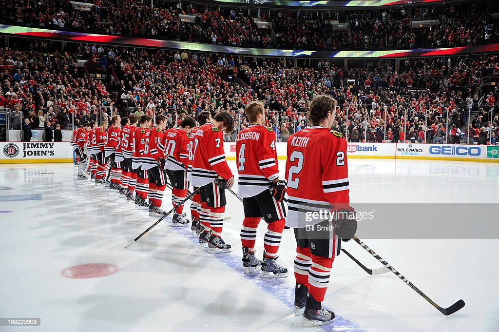 The Chicago Blackhawks stand for the 'Star Spangled Banner' before the NHL game against the St. Louis Blues on January 22, 2013 at the United Center in Chicago, Illinois.