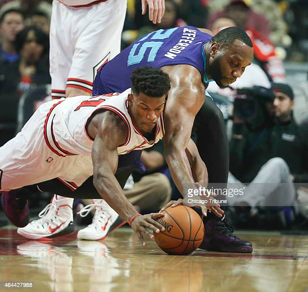 The Chicago Bulls' Jimmy Butler and the Charlotte Hornets' Al Jefferson go after a loose ball during the first half at the United Center in Chicago...