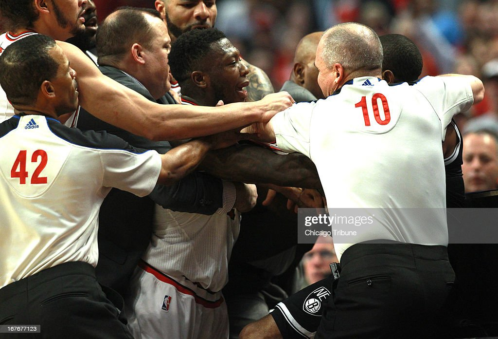 The Chicago Bulls' Nate Robinson, middle, is restrained by his coach, Tom Thibodeau, as he goes after the Brooklyn Nets' C.J. Watson during the first half on Saturday, April 27, 2013, in Game 4 of the Eastern Conference Playoffs first-round series at the United Center in Chicago, Illinois. Chicago won in triple overtime, 142-134.