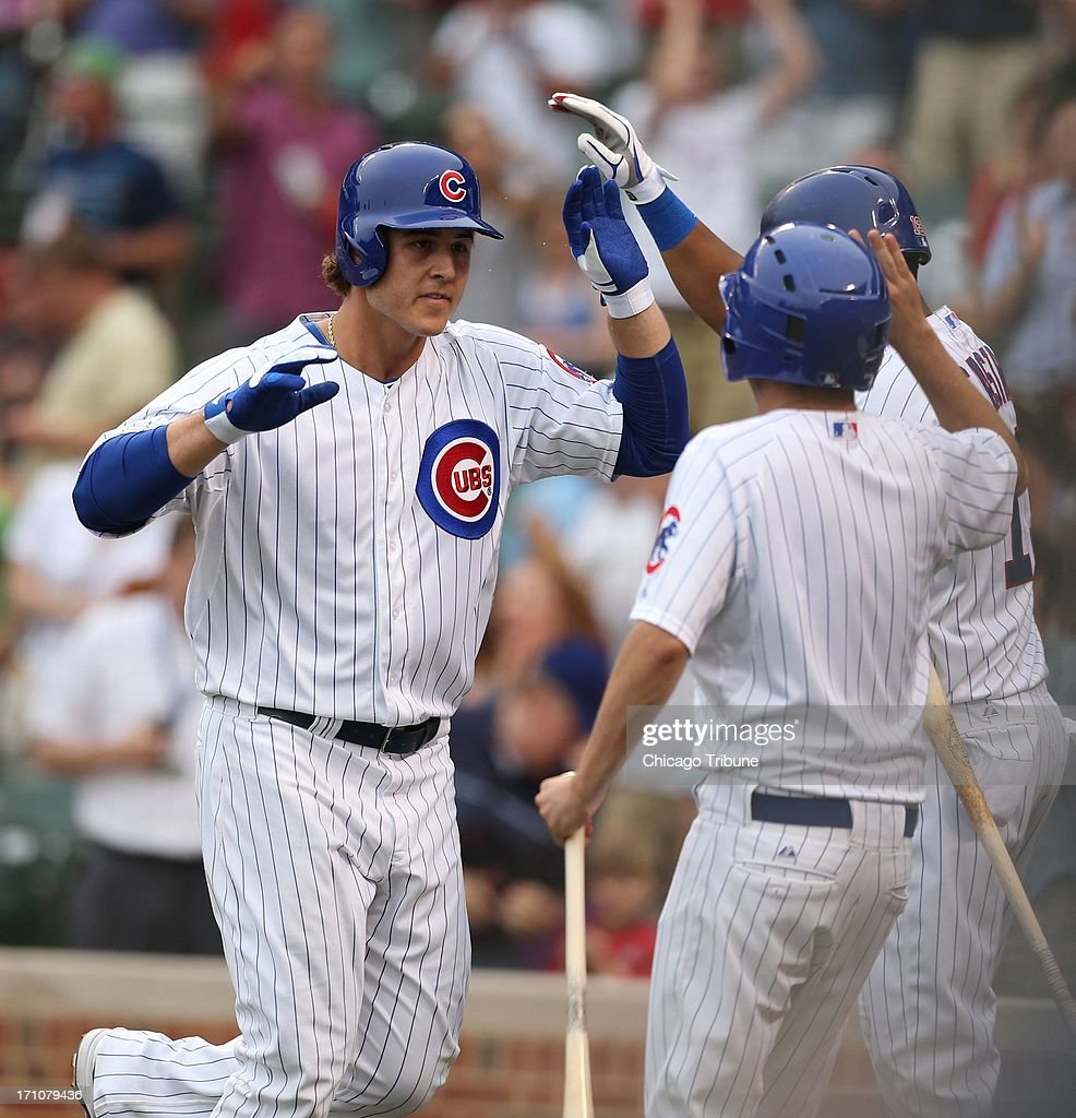 The Chicago Cubs' Anthony Rizzo, left, is greeted after his solo home run against the Houston Astros in the fourth inning at Wrigley Field in Chicago, Illinois, on Friday, June 21, 2013.
