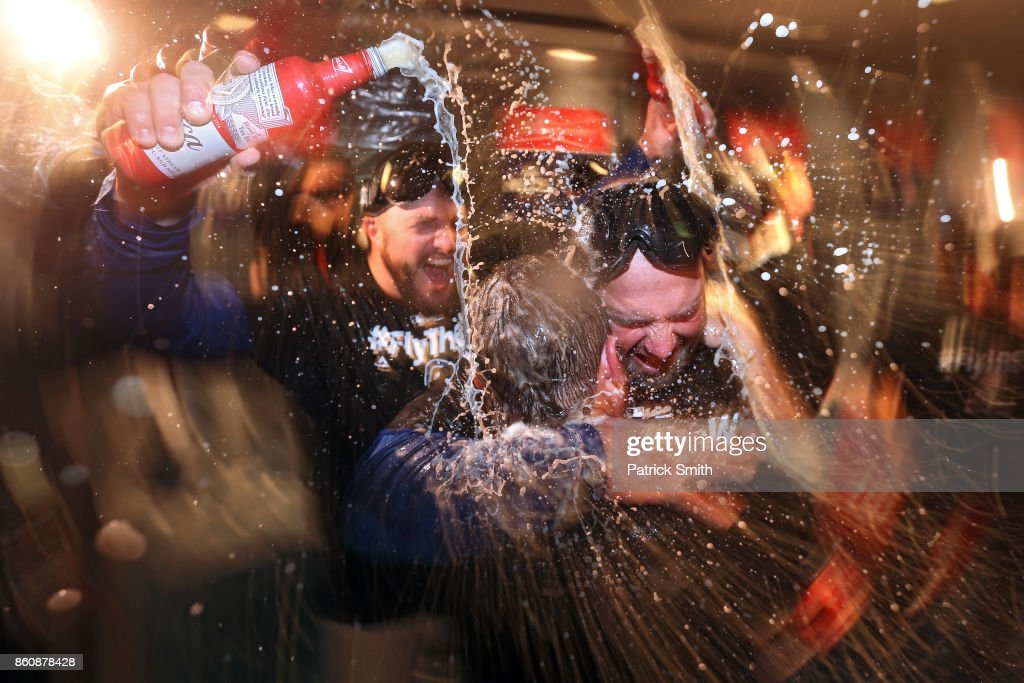 The Chicago Cubs celebrate in the locker room after defeating the Washington Nationals, 9-8, in game five of the National League Division Series at Nationals Park on October 13, 2017 in Washington, DC.