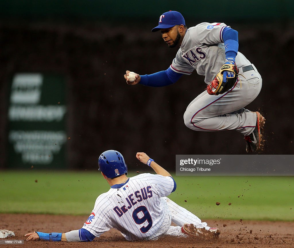 The Chicago Cubs' David DeJesus (9) breaks up a double play attempt by Texas Rangers shortstop Elvis Andrus in the eighth inning on Thursday, April 18, 2013, at Wrigley Field in Chicago, Illinois. The Cubs won, 6-2.