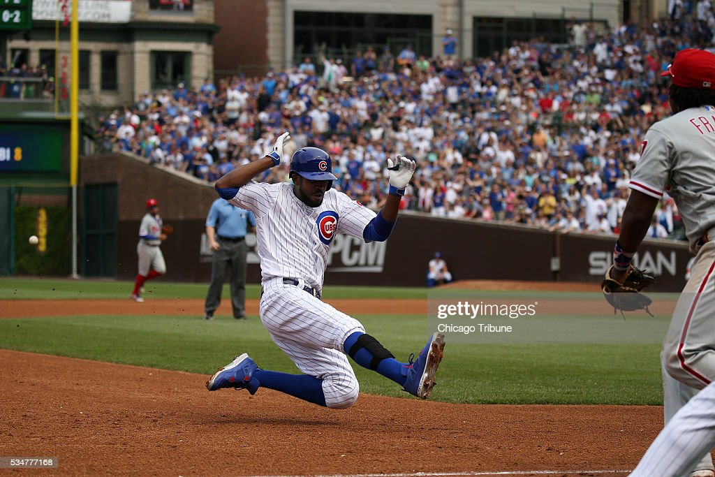The Chicago Cubs' Dexter Fowler dives into third base with a triple in the fourth inning against the Philadelphia Phillies on Friday, May 27, 2016, at Wrigley Field in Chicago.