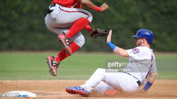 The Chicago Cubs' Ian Happ steals second base underneath Washington Nationals shortstop Wilmer Difo in the seventh inning at Wrigley Field in Chicago...