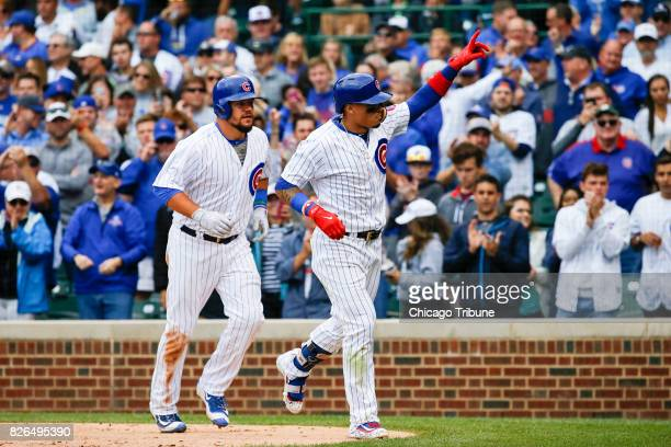 The Chicago Cubs' Javier Baez points after hitting a tworun home run as teammate Kyle Schwarber looks on in the seventh inning against the Washington...