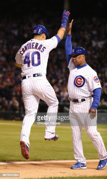 The Chicago Cubs' Willson Contreras highfives third base coach Gary Jones after his secondinning solo home run against the Los Angeles Dodgers during...