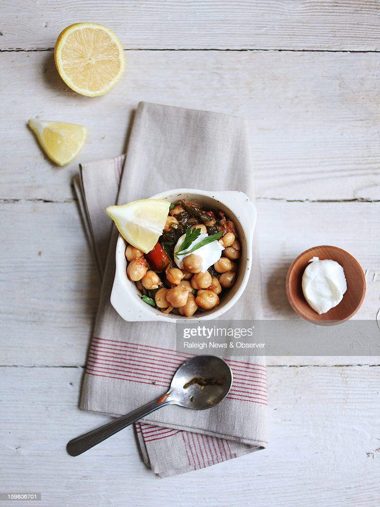 The Chick Pea Stew is topped with lemon wedges and drained yogurt.