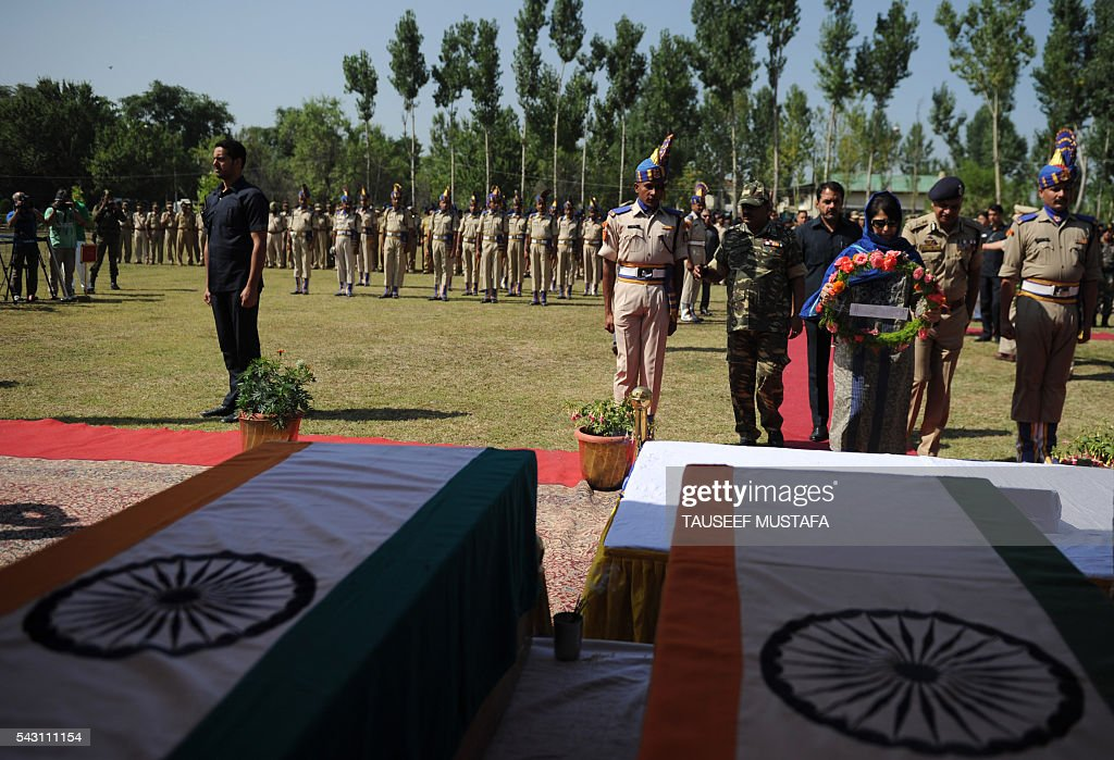 The Chief Minister of the state of Jammu and Kashmir Mehbooba Mufti (R) lays a wreath during a ceremony for eight Indi\an paramilitary soldiers killed in an ambush in Srinagar on June 26, 2016. At least eight Indian paramilitary soldiers and two suspected rebels were killed June 25 near Srinagar in India-administered Kashmir when a group of armed militants ambushed the soldiers' convoy, police said. Four militants sprayed bullets on the convoy carrying members of India's Central Reserve Police Force (CRPF) near Pampore town, killing five soldiers instantly and wounding 20, inspector general of police for the region, Javaid Gillani, told AFP. / AFP / TAUSEEF