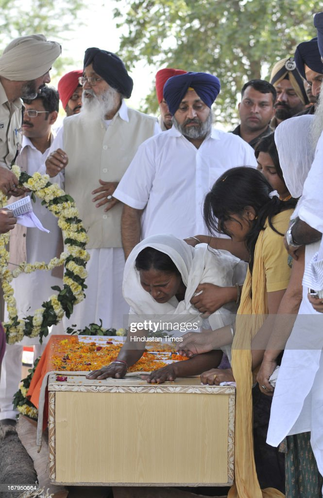 The Chief Minister Punjab Parkash Singh Badal along with Deputy Chief Minister Punjab Sukhbir Singh Badal as Sarabjit's wife Sukhpreet Kaur mourn over his body during cremation ceremony at his native village Bikhiwind on May 3, 2013 about 40 Kms from Amritsar, India. Sarabjit Singh, an Indian prisoner in Pakistan who died after being brutally assaulted in a Pakistani jail, was cremated in his native village with full state honours.