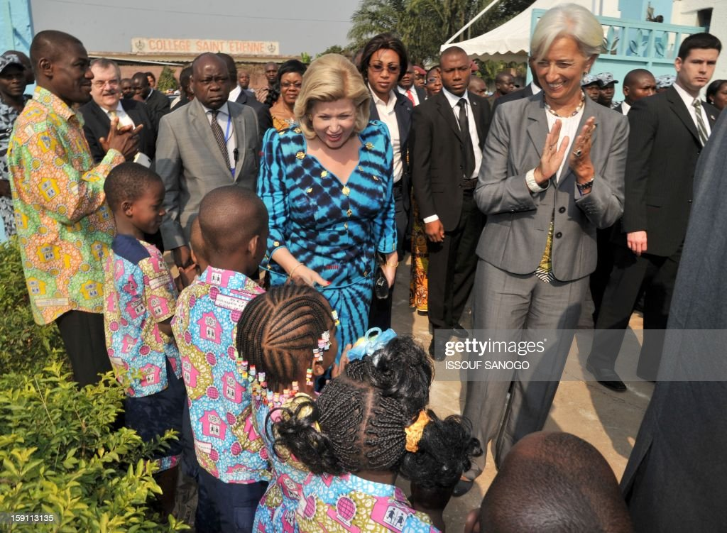 The chief of the International Monetary Fund, Christine Lagarde (R) and Ivory Coast first lady Dominique Ouattara (C) visit an orphanage village in tthe Abobo suburb of Abidjan on January 8, 2013. Lagarde, called for 'a second Ivorian economic miracle' during a visit to Abidjan as part of an African tour.