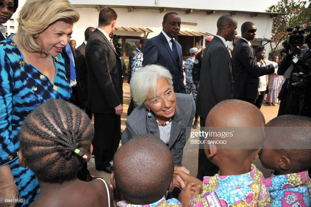 The chief of the International Monetary Fund, Christine Lagarde (C) and Ivory Coast first lady Dominique Ouattara (L) visit an orphanage village in tthe Abobo suburb of Abidjan on January 8, 2013. Lagarde, called for 'a second Ivorian economic miracle' during a visit to Abidjan as part of an African tour. AFP PHOTO / ISSOUF SANOGO